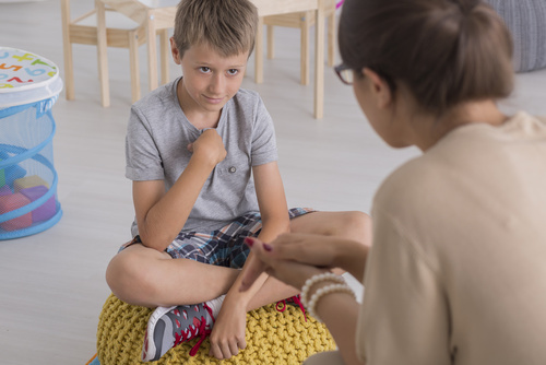 Sad young boy sitting on a pouf